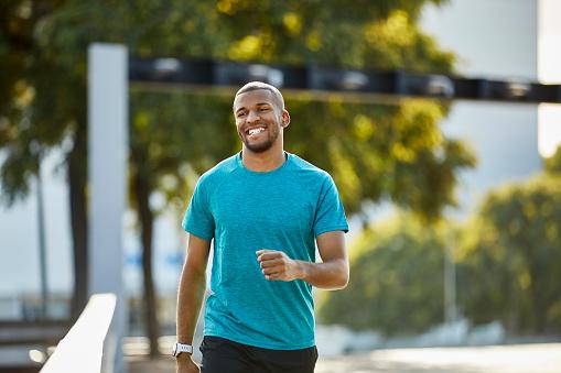 Happy man looking away while walking at park