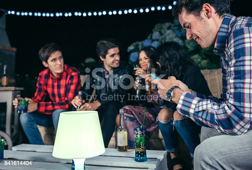 istock Happy man looking smartphone in a party with friends 841614404