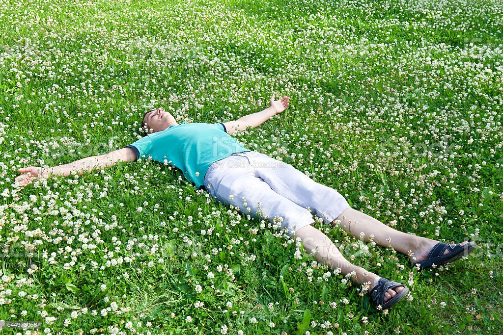 Happy man lying arms outstretched on a green meadow stock photo