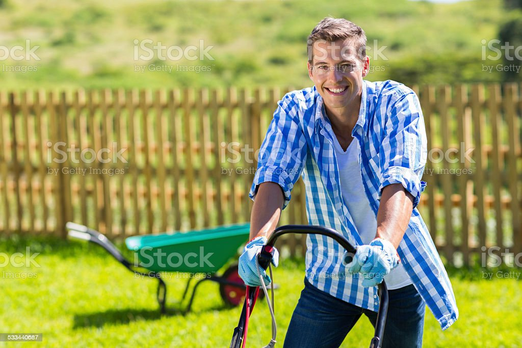 happy man mowing lawn stock photo