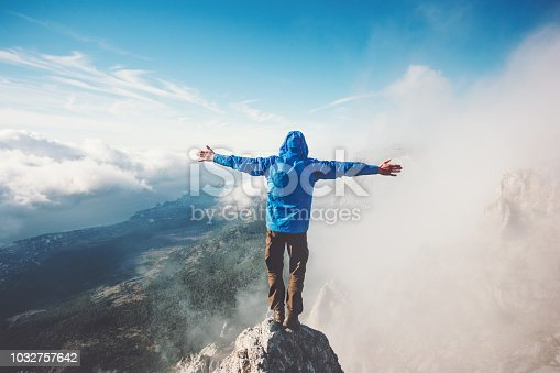 istock Happy Man on mountain summit enjoying aerial view hands raised over clouds Travel Lifestyle success concept adventure active vacations outdoor freedom emotions 1032757642