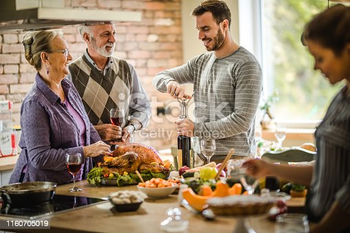 Young happy man enjoying in wine opening during Thanksgiving day at his parents' kitchen.