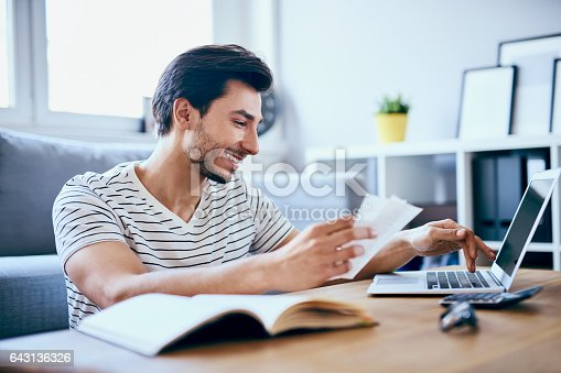 istock Happy man paying bills on his laptop in living room 643136326