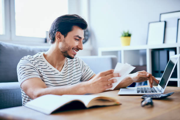 Happy man paying bills on his laptop in living room stock photo