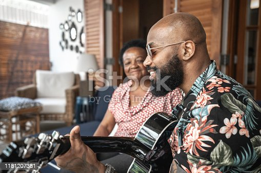 Happy man playing guitar to his mother