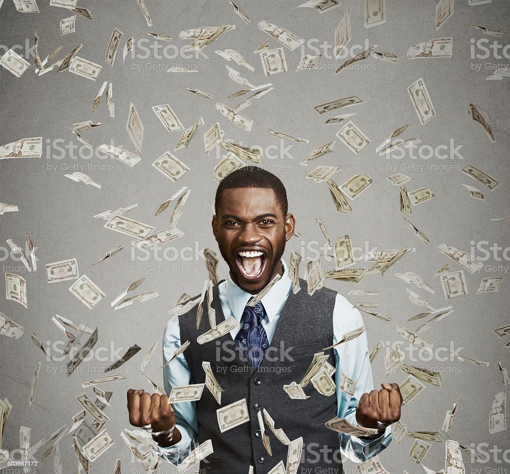 happy man pumping fists celebrates success under money rain stock photo