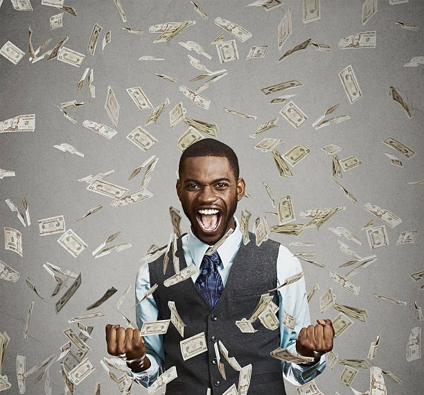 happy man pumping fists celebrates success under money rain Portrait happy man exults pumping fists ecstatic celebrates success screaming under money rain falling down dollar bills banknotes isolated gray background with copy space. Financial freedom concept millionnaire stock pictures, royalty-free photos & images