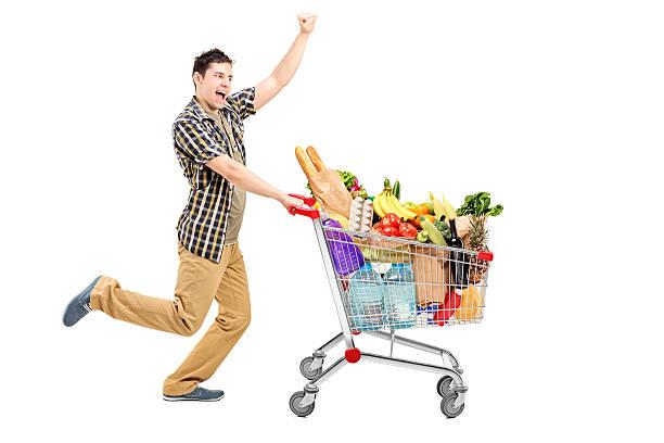 Heureux homme poussant le panier d'achats - Photo