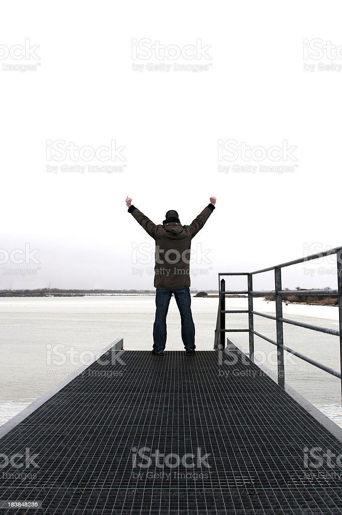 Happy man raises his arms to the sky on jetty royalty-free stock photo