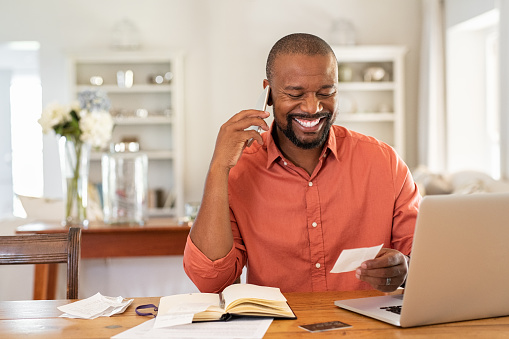 istock Happy man reading invoice and talking on phone 1152602517