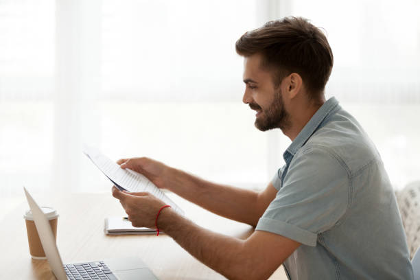 Happy man reading letter sitting at the desk stock photo