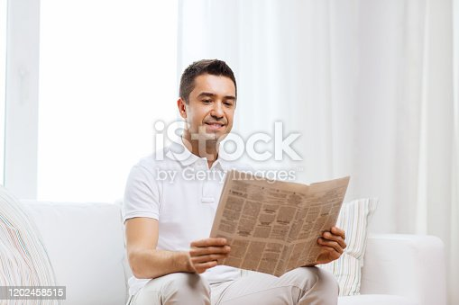 leisure, information, people and mass media concept - happy man reading newspaper at home