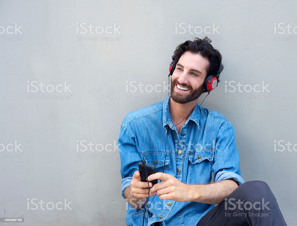 Happy man relaxing with mobile phone and headphones stock photo