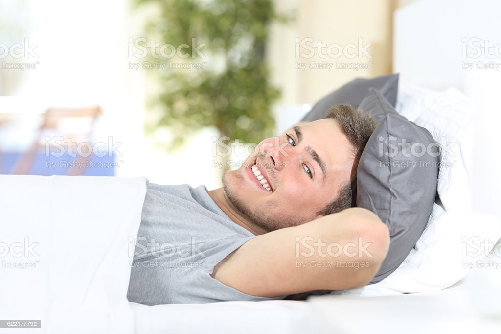 Happy man resting on a bed stock photo