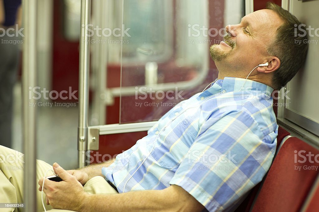 Happy Man Rides Subway Train While Listening to Music royalty-free stock photo