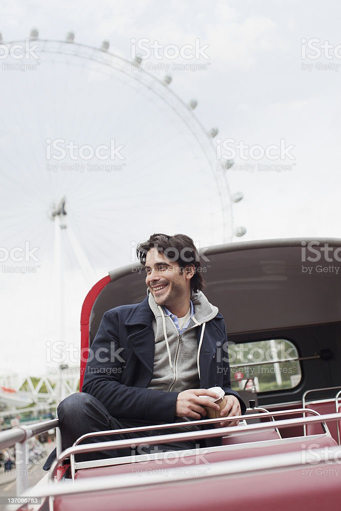 Happy man riding double decker bus in London royalty-free stock photo