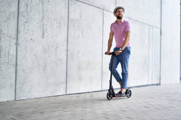 happy man riding kick scooter - electric push scooter stock photos and pictures