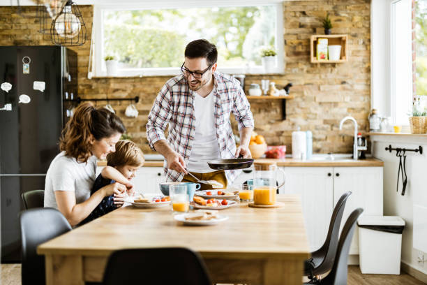 Happy man serving breakfast to his family in dining room. stock photo