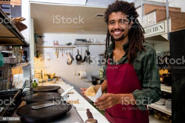 Happy man serving crepes at a restaurant picture id687360066?b=1&k=6&m=687360066&s=612x612&h=9amnngilcit7t4rls2szxkwjl8urglhe9nyqbtdaalg=