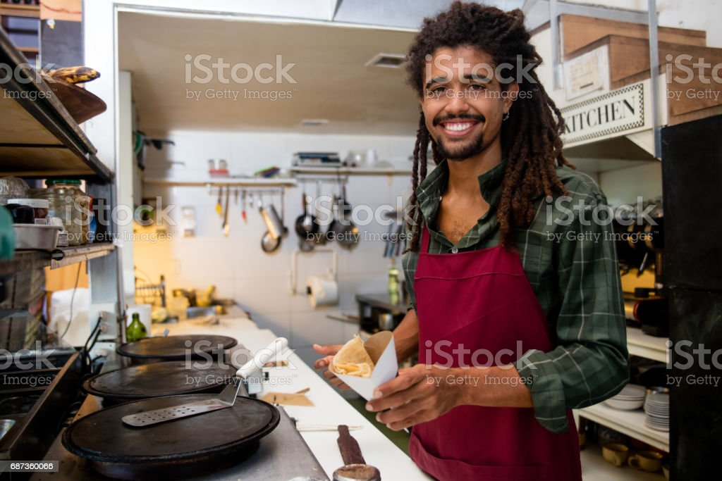 Happy man serving crepes at a restaurant stock photo
