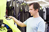 Happy man shopping for t-shirt in sport shop