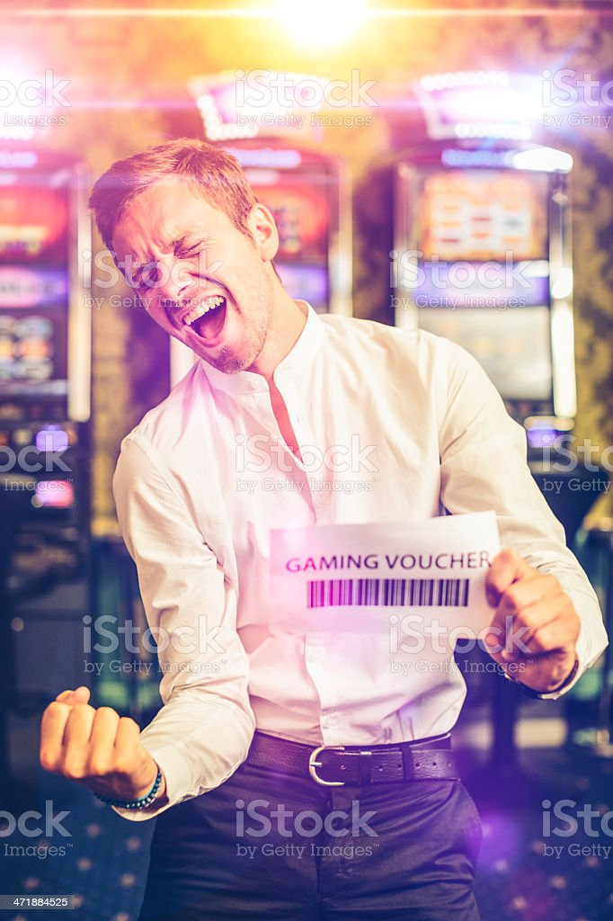 Happy Man Showing a Gaming Voucher at Casino stock photo