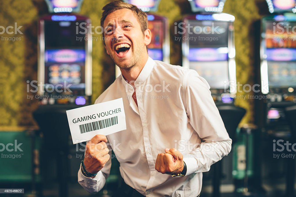 Happy Man Showing a Gaming Voucher. Slot Machine on the background....