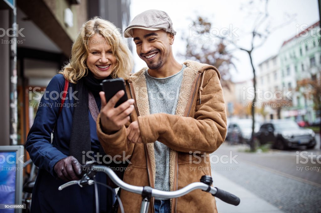 Happy man showing smart phone to friend stock photo