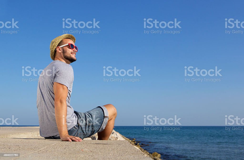 Happy man sitting by the sea with hat stock photo