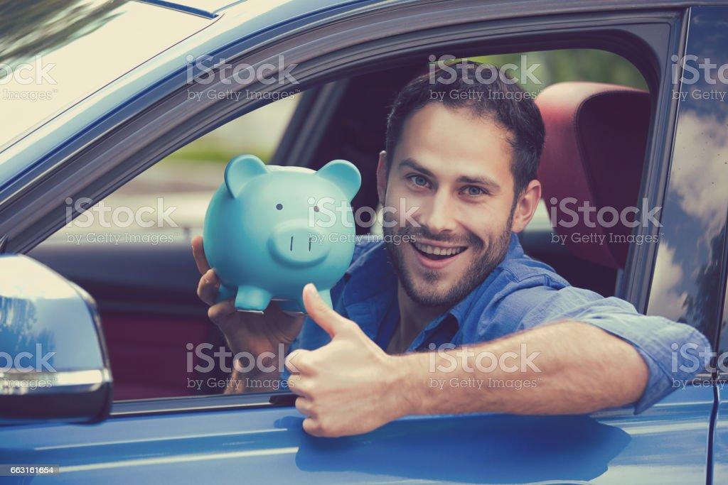 Glücklicher Mann sitzt im Inneren seines neuen Autos halten Sparschwein – Foto