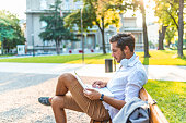 Happy man sitting on bench and using laptop in a park. Young man sitting on the park bench with laptop on his lap. Handsome businessman sitting on a wooden bench in the city with a laptop and smiling