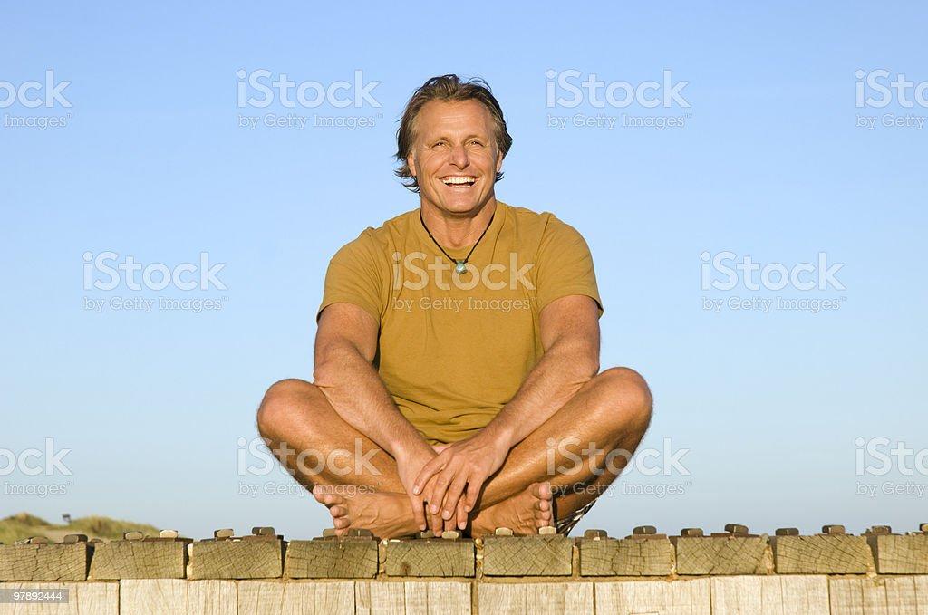 Happy man sitting on boardwalk royalty-free stock photo