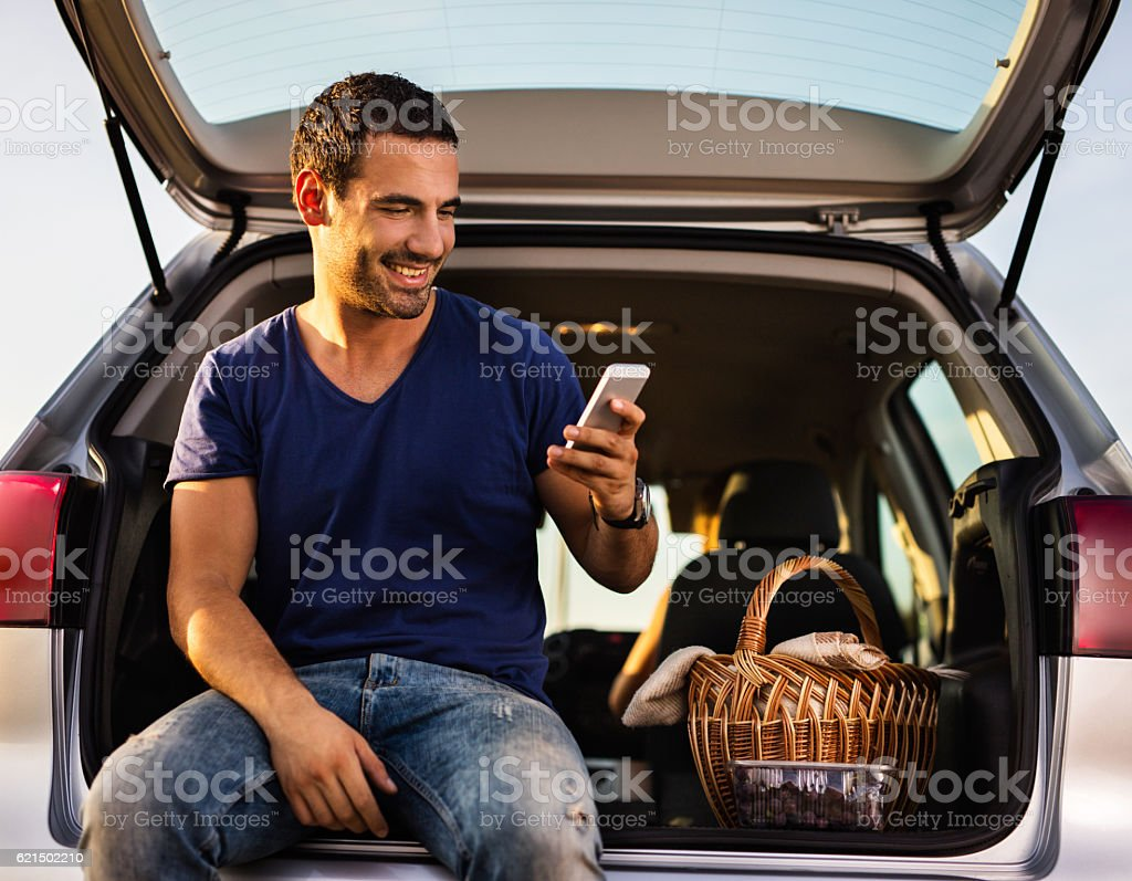 Happy man sitting on car trunk and using cell phone. foto stock royalty-free