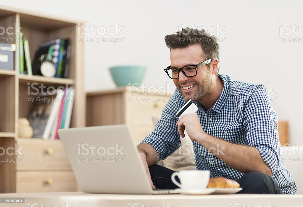 Happy man sitting on sofa with laptop and credit card stock photo