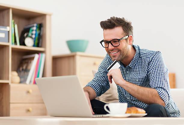 glücklicher mann sitzt auf sofa mit laptop und kreditkarte - sofa online kaufen stock-fotos und bilder