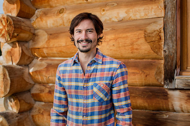 Happy man standing against log cabin Portrait of happy man standing against log cabin plaid shirt stock pictures, royalty-free photos & images