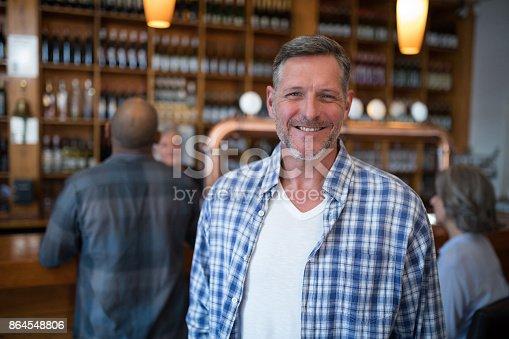 Portrait of happy man standing in bar