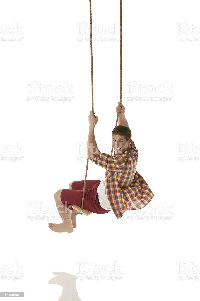 Happy man swinging on a rope swing royalty-free stock photo