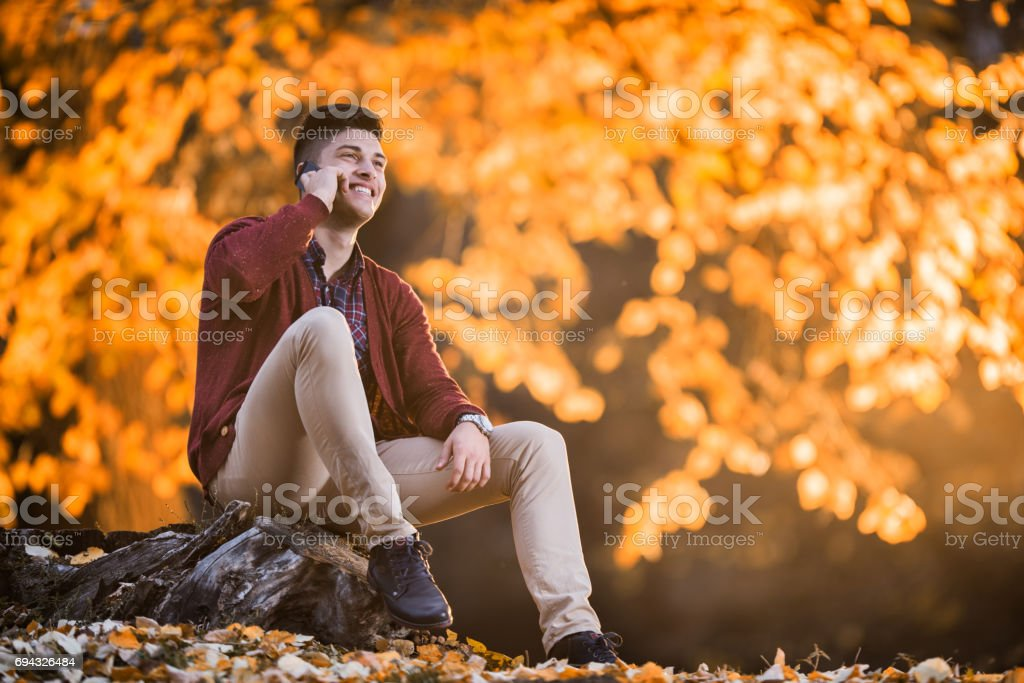 Happy man talking over mobile phone in the park. stock photo