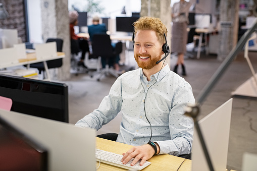 Portrait of consultant agent man in call center smiling. Happy customer support agent working with headset while sitting at his workstation. Smiling telephone operator using computer in modern open space office.