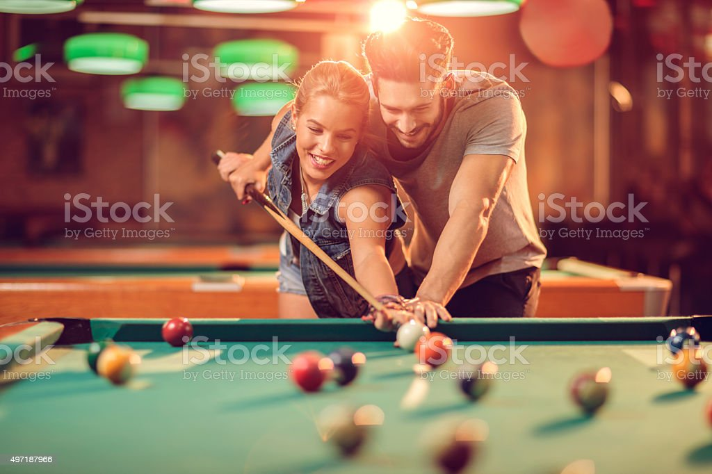 Happy man teaching his girlfriend how to play snooker. stock photo