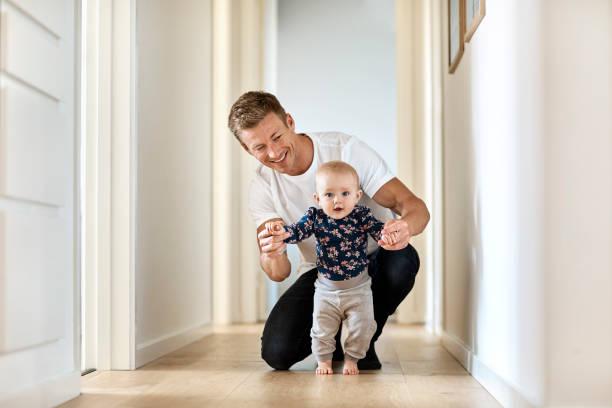 Glücklicher Mann lehrt kleinen Sohn, im Flur zu gehen – Foto