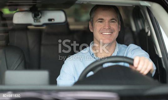 1138561232 istock photo Happy man test driving a car at the dealership 824981830