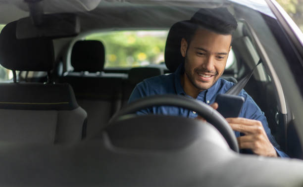 happy man texting and driving in his car - side hustle stock pictures, royalty-free photos & images
