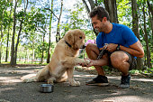 Happy Brazilian man training with his dog at the park asking him to give his paw - lifestyle concepts