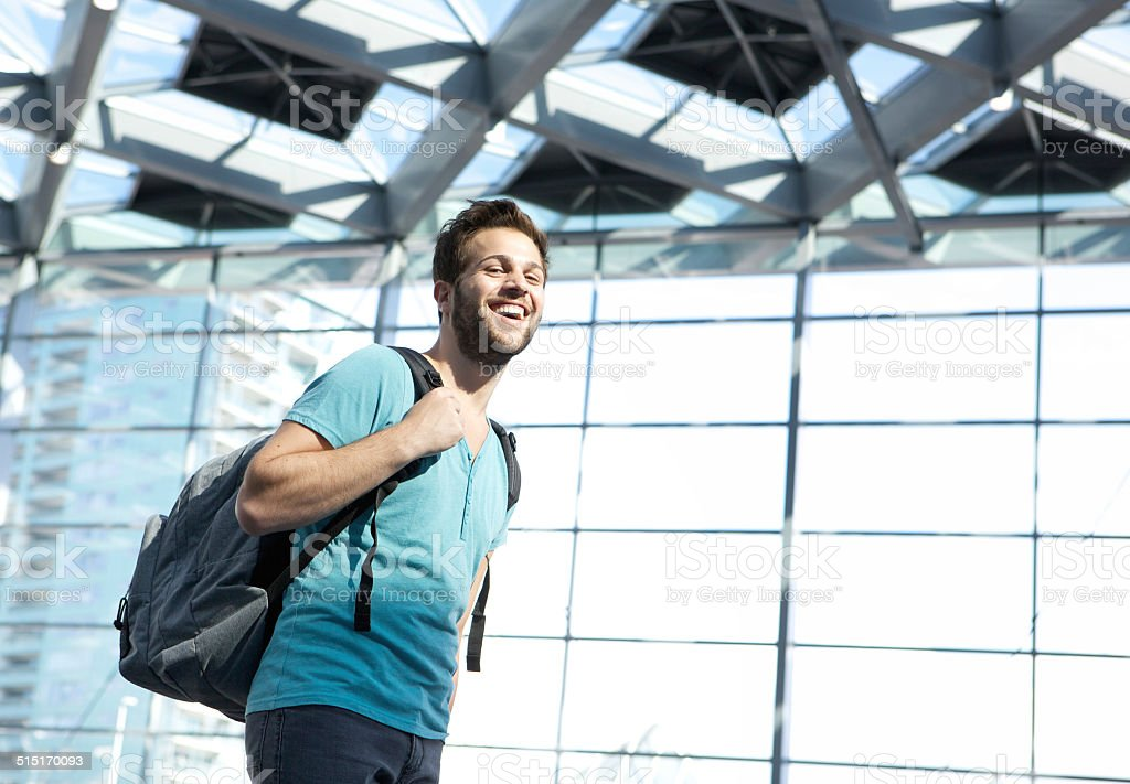 Happy man traveling with bag in airport stock photo