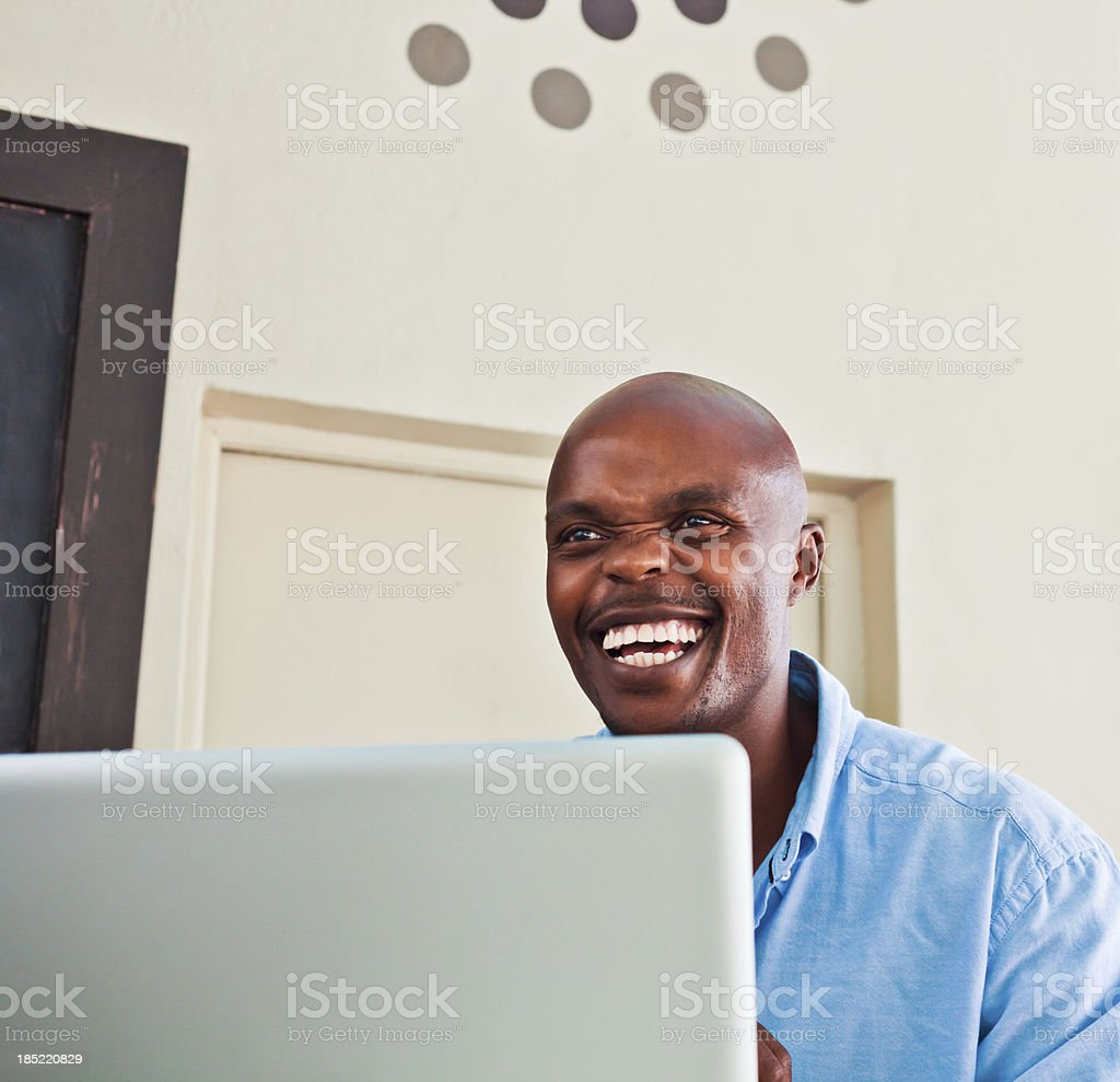 Happy man using laptop Laughing african man using laptop at home. Adult Stock Photo