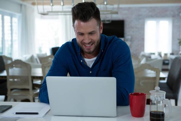 glücklicher mann mit laptop  - schwarzer kaffee net stock-fotos und bilder