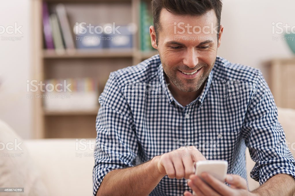 Happy man using mobile phone at home in living room stock photo