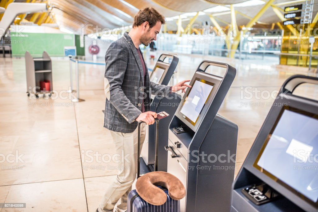 happy man using the check-in machine at the airport getting the boarding pass. happy man using the check-in machine at the airport getting the boarding pass. Adult Stock Photo